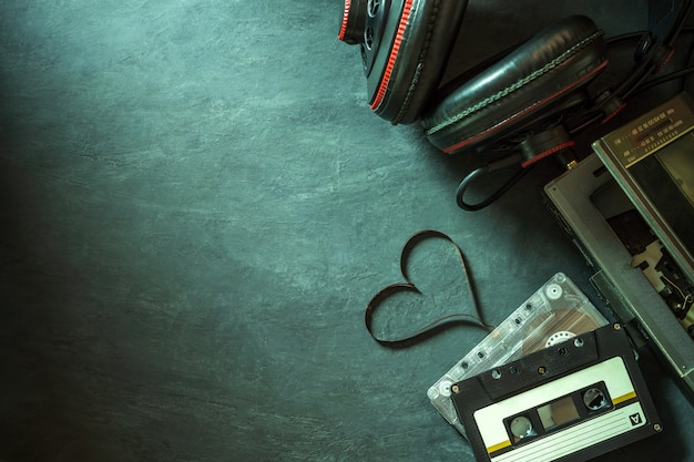 Cassette player and headphone on cement floor. heart shape of cassette tape strip.
