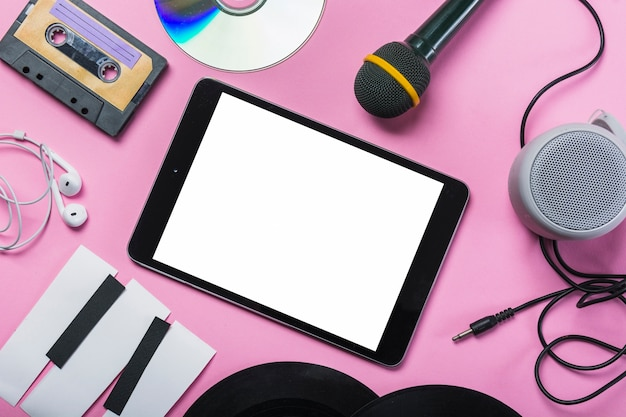 Cassette tape; cd; earphone; vinyl record; microphone; speaker; paper piano keys around the digital tablet on pink background