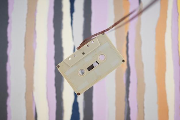 Кассета, классическая винтажная античная квартира ностальгии лежала на разорванном фоне цветной бумаги.