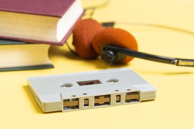 노란색 배경에 카세트 테이프, 헤드폰 및 책.