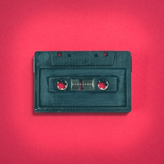 Cassette tape on red background, top view