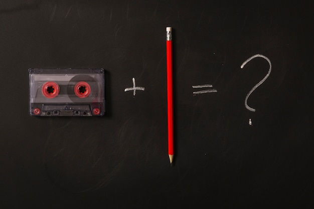 Cassette tape plus red pencil equals to question mark on black background