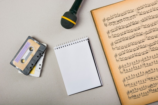 Кассета; спиральный блокнот и микрофон со старым старинным музыкальным ноутбуком