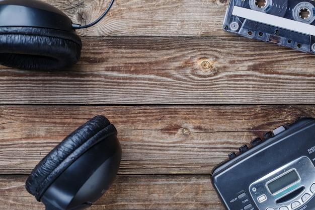 나무 테이블 위에 카세트 테이프, 카세트 플레이어, 헤드폰. 평면도. 텍스트, 로고 등을 위한 빈 공간이 있는 레트로 개념