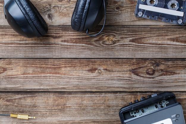 Кассеты, магнитофон и наушники над деревянным столом. вид сверху. ретро-концепция с пустым пространством для текста, логотипа и т. д.