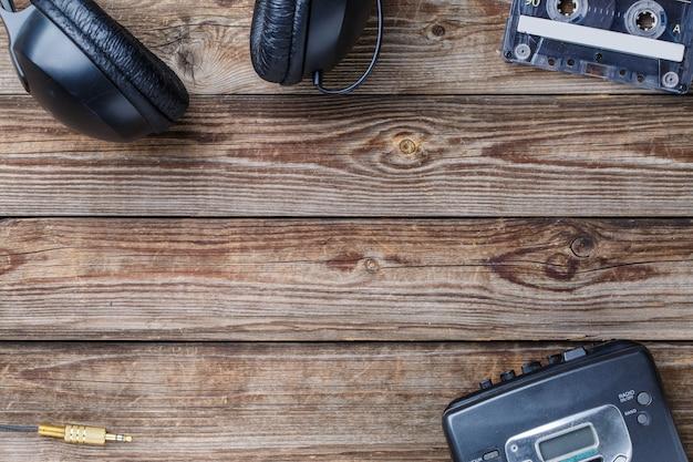 木製のテーブルの上にカセットテープ、カセットプレーヤー、ヘッドフォン。上面図。テキスト、ロゴなどのための空きスペースを持つレトロなコンセプト。