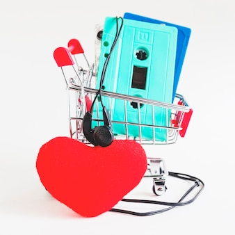 Cassette tapes in shopping trolley with earphone and red heart against white backdrop