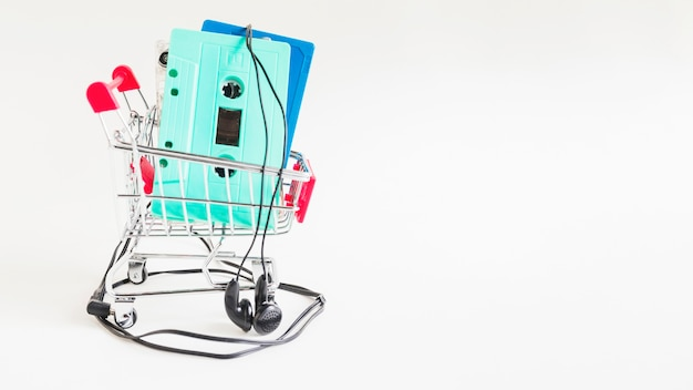 Cassette tapes in shopping trolley with earphone against white backdrop