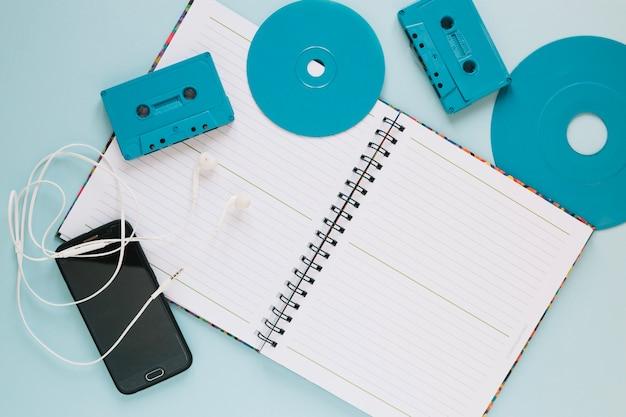 Кассеты и диски возле ноутбука и смартфона
