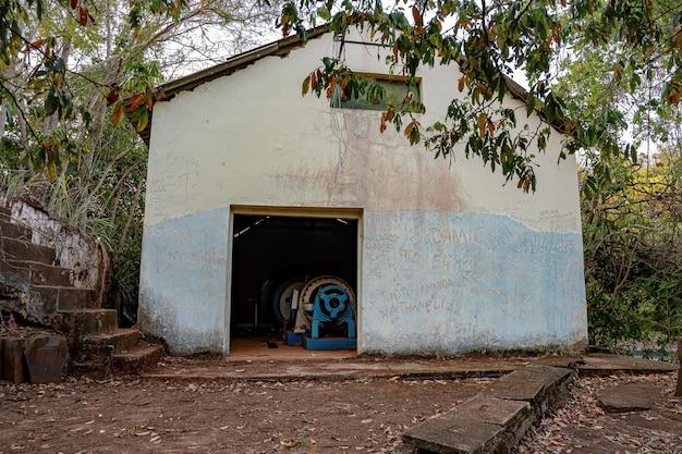 Cassilandia, mato grosso do sul, brazil - 09 03 2021: 브라질 도시 cassilandia에 있는 강 apore의 가을에 버려진 작은 수력 발전소의 엔진룸