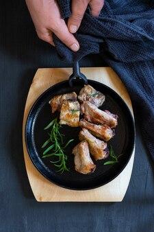 검은 색 또는 파란색 배경, 평면도에 튀긴 돼지 고기와 주철 블랙 라운드 팬.