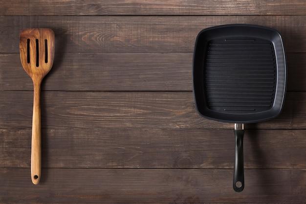 Чугунная сковорода и шпатель на деревянных фоне.