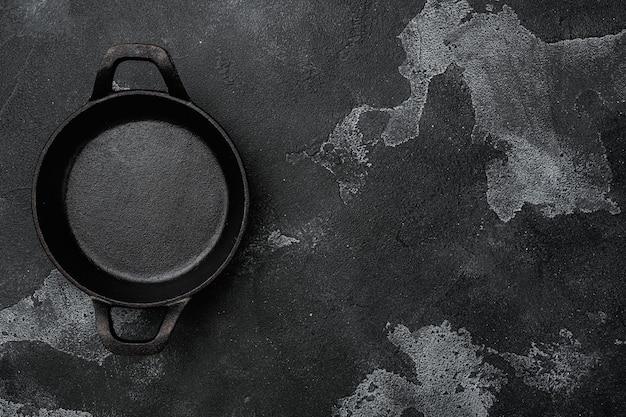 Чугунная сковорода с копией пространства для текста или еды с копией пространства для текста или еды, плоская планировка, вид сверху, на черном фоне темного каменного стола