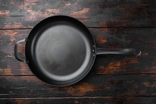 Чугунная сковорода с копией пространства для текста или еды с копией пространства для текста или еды, плоская планировка, вид сверху, на фоне старого темного деревянного стола