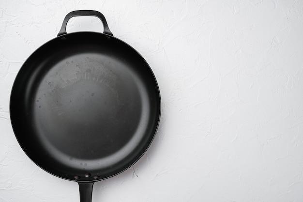 Чугунная сковорода с копией пространства для текста или еды с копией пространства для текста или еды, плоская планировка, вид сверху, на фоне белого каменного стола