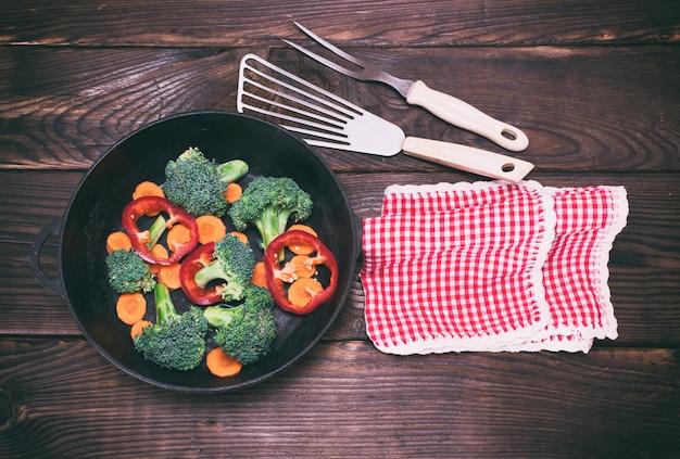 Чугунная сковорода с кусочками моркови, брокколи