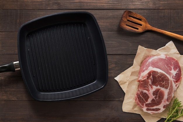 Cast iron griddle pan and beef steak wood on wooden background. top view, copy space.