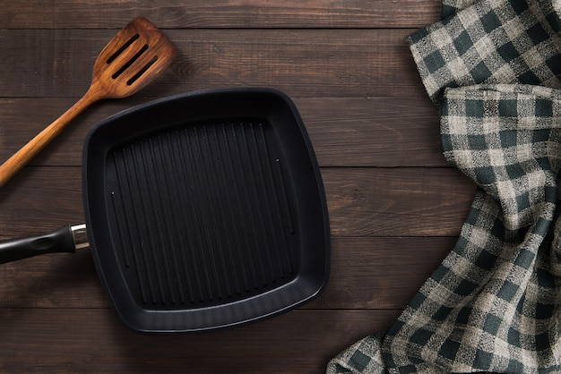 Cast iron griddle pan and turner wood on wooden background. top view, copy space.
