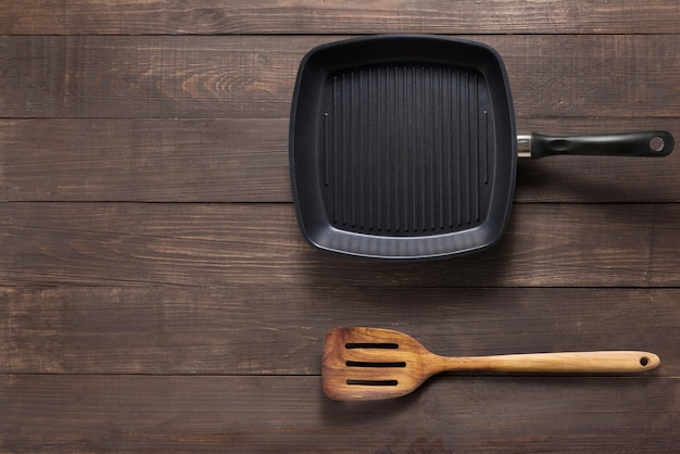 Cast iron griddle pan and turner wood on wooden background