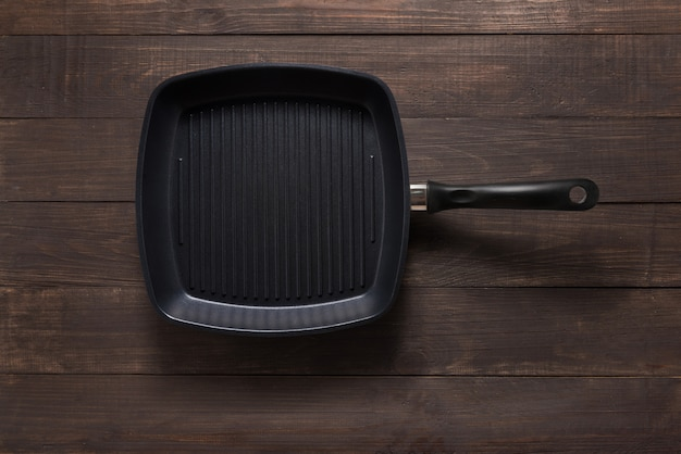 Cast iron griddle pan on wooden background