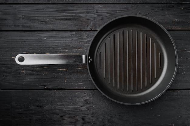 Чугунная сковорода для гриля с копией пространства для текста или еды с копией пространства для текста или еды, плоская планировка, вид сверху, на черном фоне деревянного стола