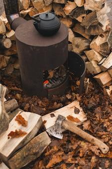 Чугунный чайник для традиционной восточной чайной церемонии на обожженной печи с красивыми осенними дубовыми листьями и сложенными бревнами на заднем плане