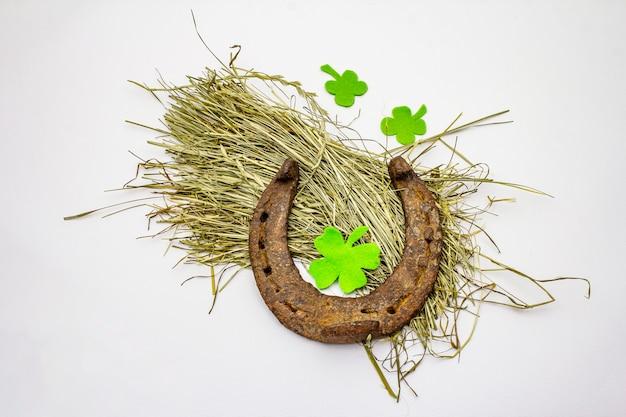 Cast iron metal horseshoe on hay, isolated on white background, felt clover leaves