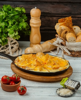 Cast iron pan of fried potatoes with eggs served with bread and cheese