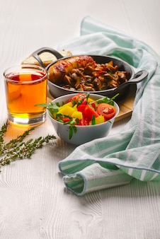 Cast-iron pan with fried sausage and mushrooms, salad with fresh vegetables and glass of juice on white wooden table.