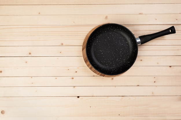 Cast iron pan on wooden table. top view