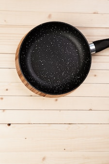 Cast iron pan on wooden table.