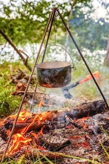 Cast iron pot cooks over open fire in a campsite in forest in sunny summer day