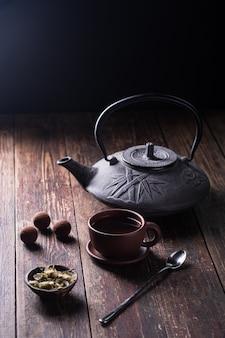 鋳鉄製のティーポット、プラムジャム、暗い背景にデザートスプーン