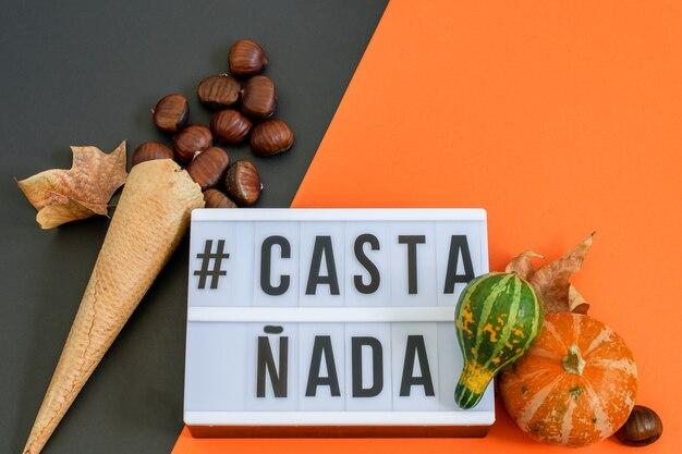 Текст castañada с вафельным рожком мороженого с каштанами, декоративные тыквы на черно-оранжевой бумаге. плоская планировка