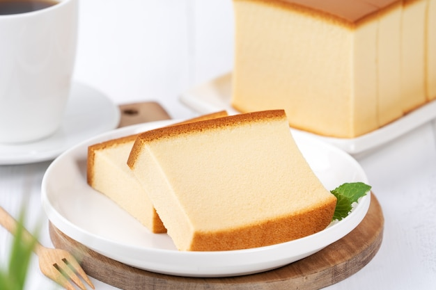 Castella (kasutera) - beautiful delicious japanese sliced sponge cake food on white plate over rustic white wooden table, close up, copy space design concept.