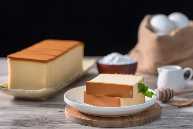 Castella kasutera 소박한 나무 테이블 위에 하얀 접시에 맛있는 일본 슬라이스 스폰지 케이크 음식은 건강한 식생활 복사 공간 디자인을 닫습니다