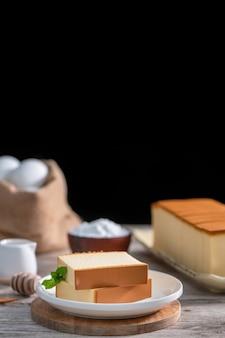 Castella (kasutera)-소박한 나무 테이블 위에 하얀 접시에 맛있는 일본 썰어 스폰지 케이크 음식, 가까이, 건강 한 식습관, 복사 공간 디자인.