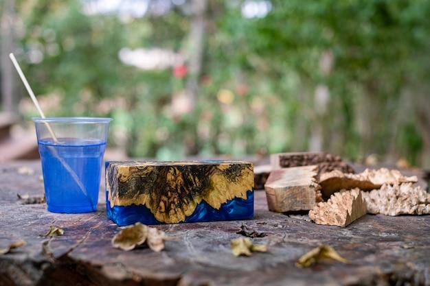 古いテーブルに青いエポキシ樹脂バールウッドキューブをキャスト