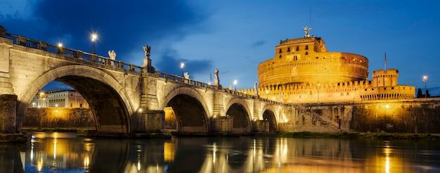 Замок святого ангела и святой ангел мост через реку тибр в риме ночью.