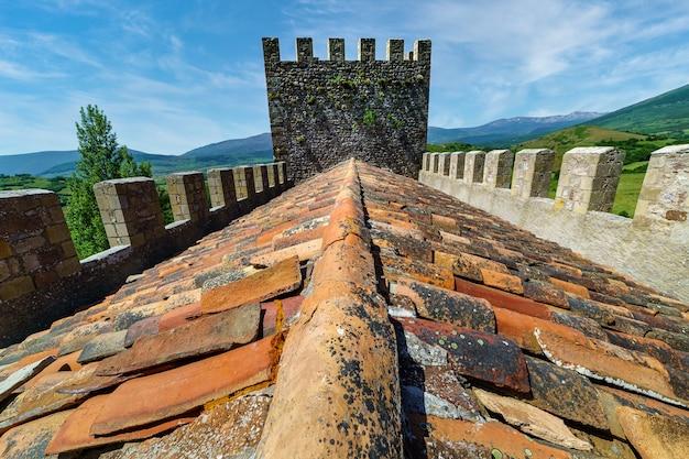Крыша замка с черепицей различных цветов и башня на заднем плане. argueso santander.