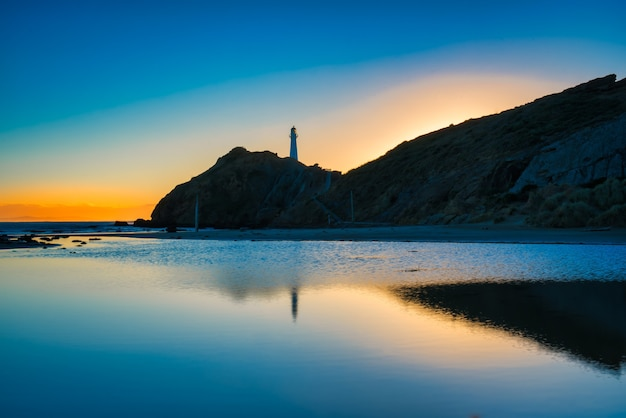 Castlepoint 등대와 해가 새벽에 떠오를 때 라군의 잔잔한 물에 비치는 햇빛의 초기 신호
