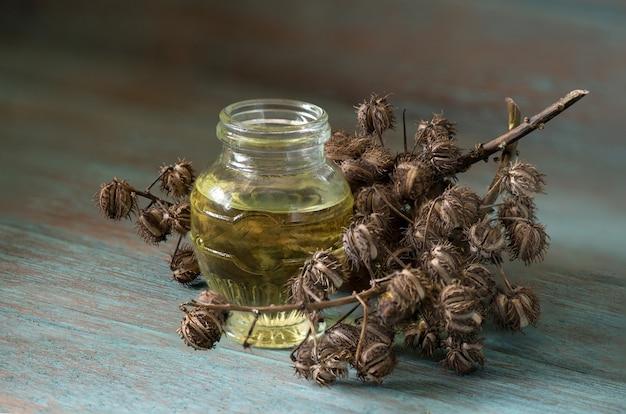 ひまし油、古い木製のテーブルにドライフルーツとオイル。