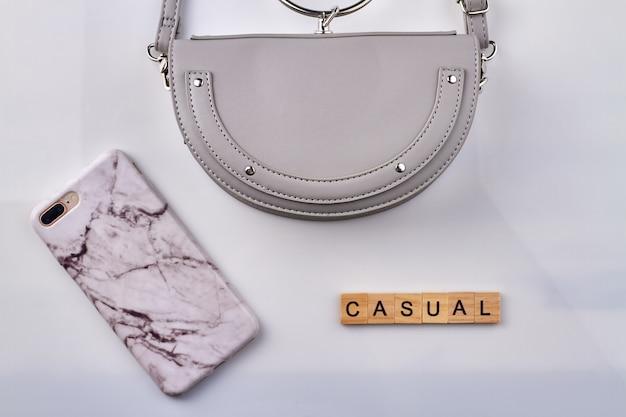 캐주얼 액세서리 개념 평평하다. 여자 핸드백과 스마트 폰 흰색 배경에 고립.