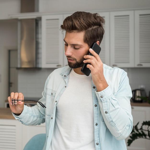 Maschio adulto casuale che comunica sul telefono