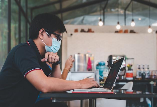 Повседневный азиатский деловой человек в маске для лица работает, глядя на данные о ценах на онлайн-биржу на портативном компьютере