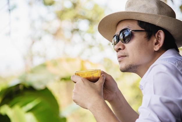 Случайный азиатский мужчина пьет горячий кофе счастливо в природе