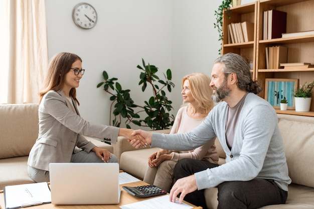 Casual bearded man shaking hand of young female real estate agent over desk while making deal and signing papers
