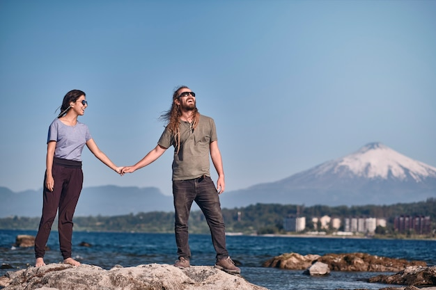 Casual beautiful couple with dreadlocks walking hand in hand on some stones floating in a lake