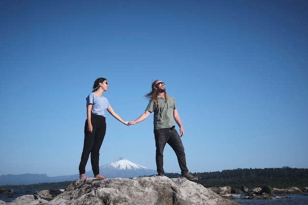 Casual beautiful couple with sunglasses and dreadlocks walking hand in hand on some stones