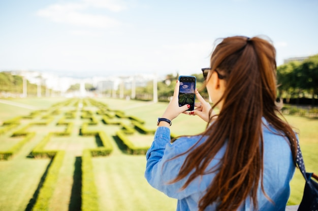 夏の都市庭園公園でスマートフォンの写真のポーズをとってカジュアルな美しい若い女性。